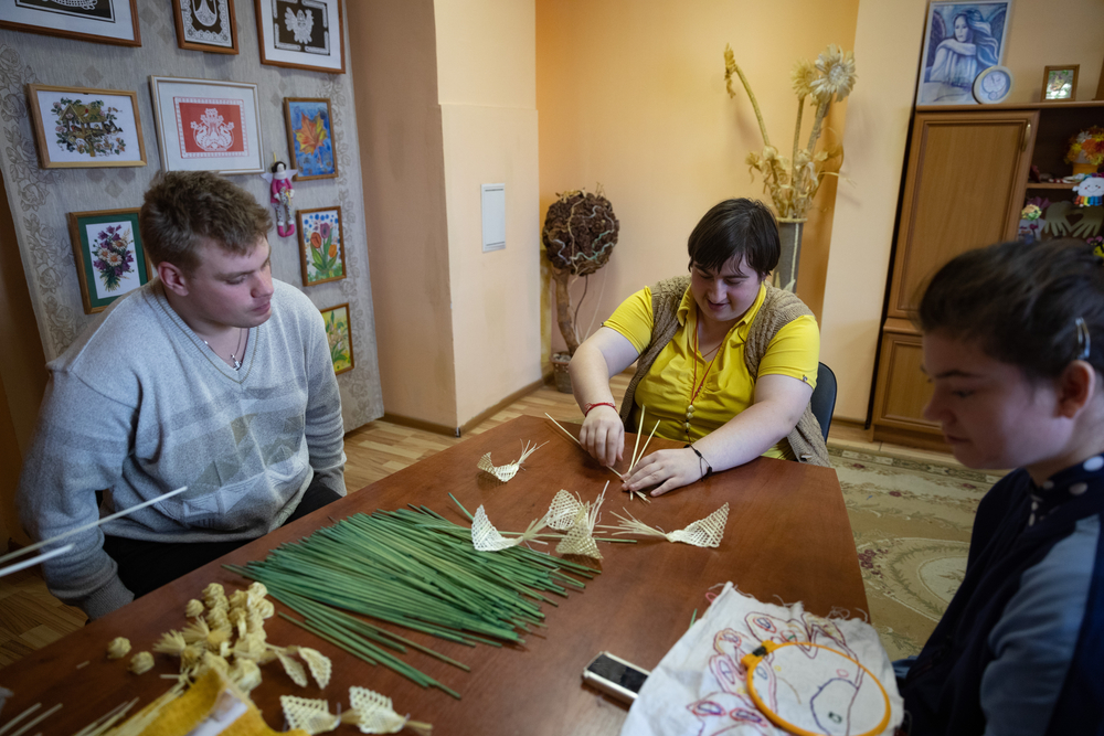 Young adults with disabilities around a table doing crafts.