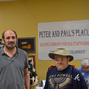 Two men in front of a sign about Peter and Paul's Place.